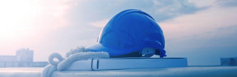 Blue hard hat on design papers