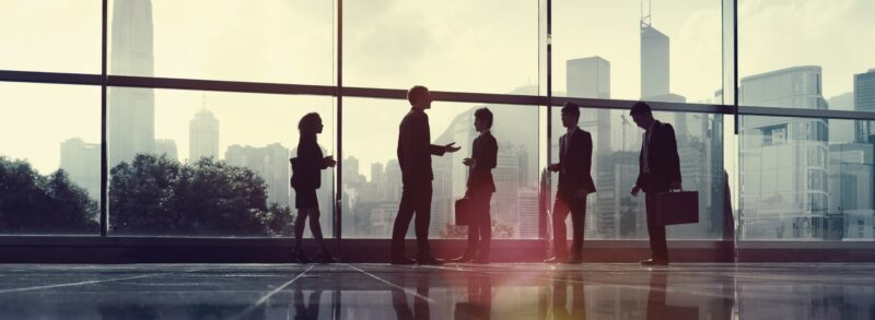 About us - image of business people in conversation in office building