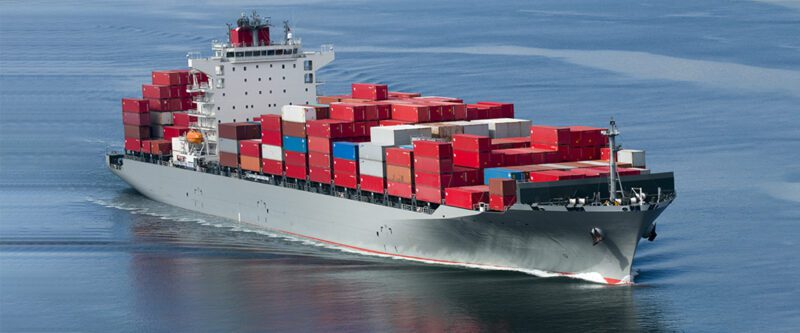 Marine Insurance - Image of container ship at sea with mostly red containers