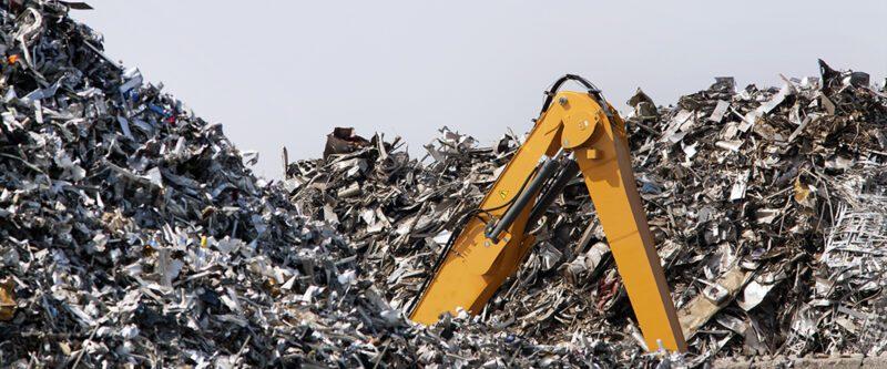 Scrap metal Recycling Insurance | Image of Metal scrapyard with buried excavator