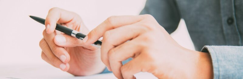 Commercial Insurance Solutions - two hands with a pen in hand ready to sign a paper