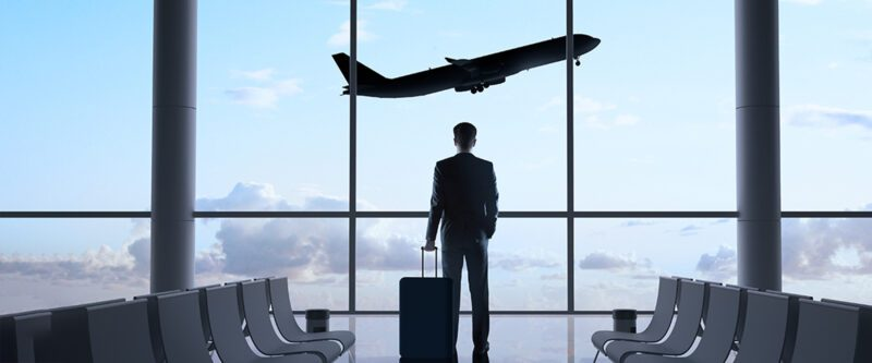 Business Travel Accident Insurance - Business Man at Airport with flying plane in background