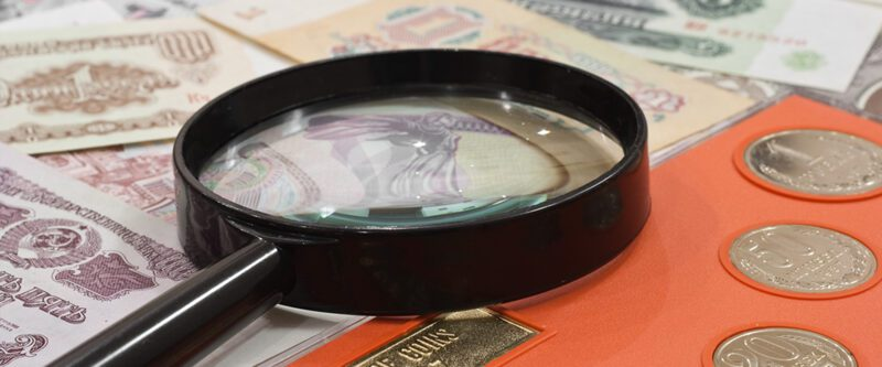 Coins Insurance | Coins and Paper Money under a Magnifying glass.
