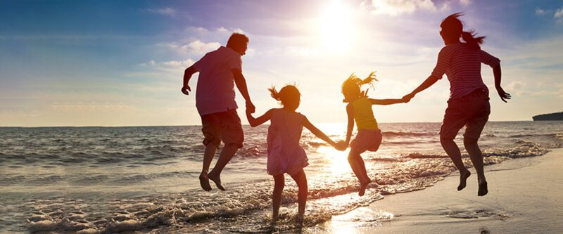 Personal Umbrella Insurance to protect your family - image of jumping family on the beach