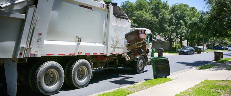 Waste hauler insurance | Garbage Truck in nice neighborhood