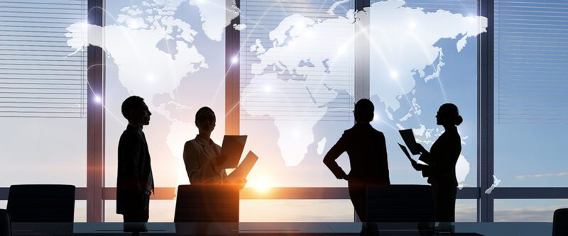 International Insurance Programs - Image of Silhouette of business people in meeting room in front of world map