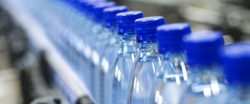 Product Recall Insurance lastic bottles with blue line on factory assembly line