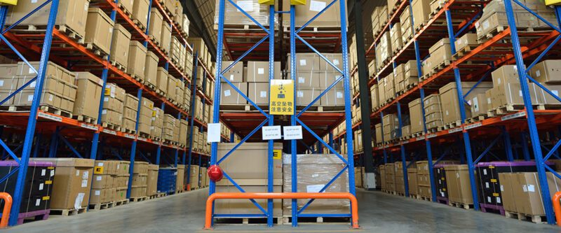Supply Chain Insurance - Inside Retail Distribution Warehouse - Interior of warehouse with blue metal shelving holding cardboard boxes